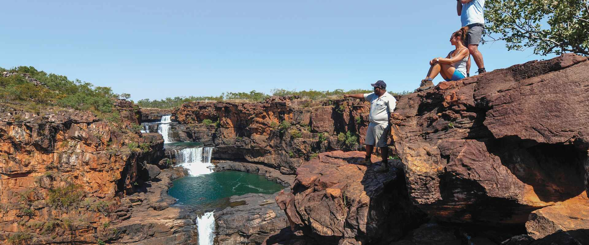 View of two passengers looking over the falls with a guide, Western Australia
