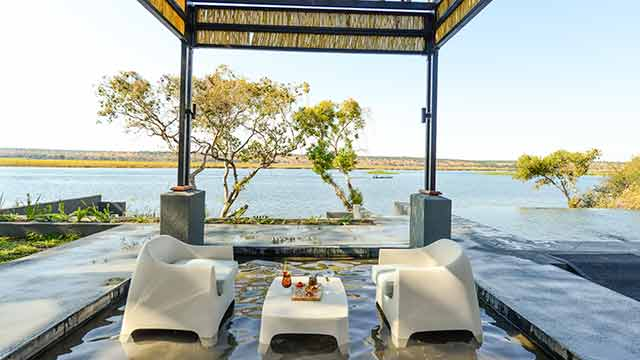 Table setting under a canopy overlooking the water, Botswana