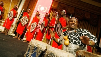 Man playing drums along with Kenyan singers performing