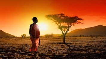 Kenyan tribesman standing on one foot holding spear in hand at sunset