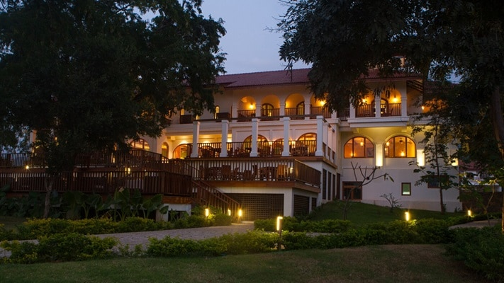 Night time view of two storey luxury hotel set among the lush green gardens and mature trees