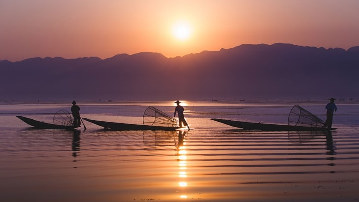 Three fishermen fishing on a lake at sunrise, Myanmar