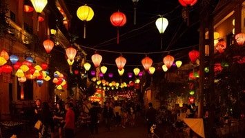 Upward view of colourful lanterns hanging in the night sky, Asia