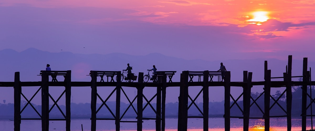 Locals and their carts crossing a bridge silhouetted against the purple hues as the sunsets, Myanmar