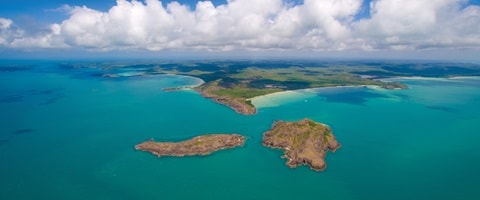 Aerial view of crystal clear blue waters with land in the distance, QLD