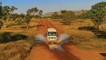 4wd coach driving on dirt road in outback, wa