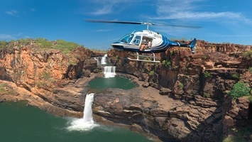 Helicopter flight over the rugged cliff face viewing the tiered water fall