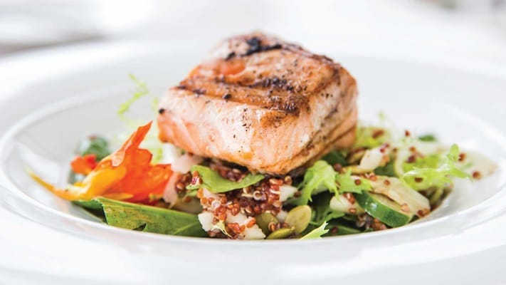 Salmon resting on a bed of salad on white plate