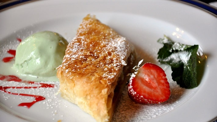 Plate with strudel, icecream and a strawberry