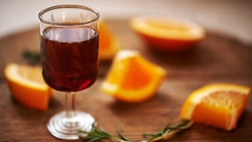 Filled glass of wine sitting on wooden board with orange segments