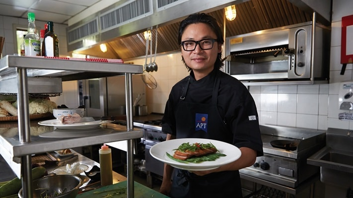 Chef Luke Nguyen holding a plate of food whilst standing in a kitchen