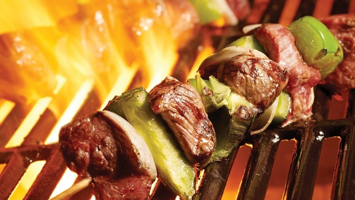Meat and vegetable shish kebab over a flaming grill
