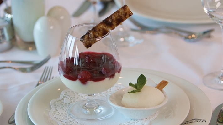 Dessert glass of berries and cream with a side dish of Icecream