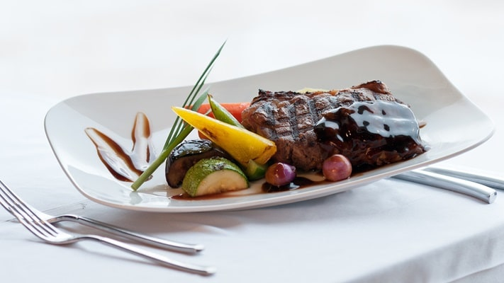 Rib steak with seasonal roast vegatables on plate with cutlery