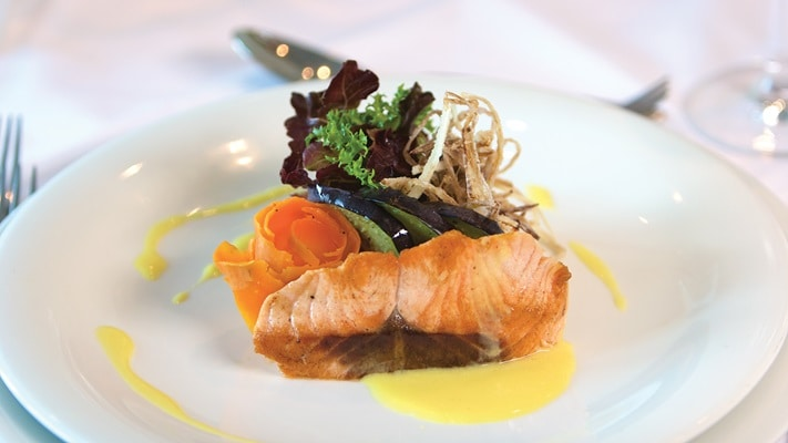 Single plate of salmon and salad with lemon sauce