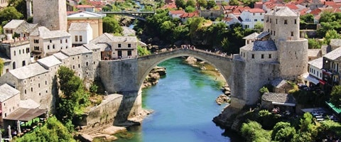 View of old town set on a river with huge bridge, Bosnia