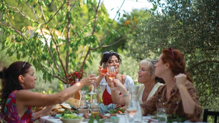 Group of ladies drinking wine and dining at a table outdoors in Croatia.