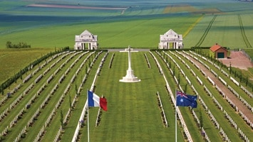 Aerial view of the rolling green hills and the flags flying above the Somme war cemetery