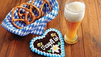 Decorated heart shape cookie, bowl of pretzels and a glass of beer sitting on a table