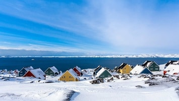 Colorful houses dotted along the coastline covered in snow