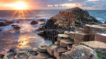 Cluster of rocks and wooden structures on waters edge at sunset, Ireland