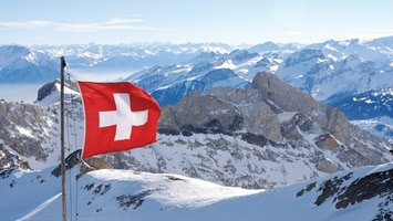View of Swiss Alps mountaintop with flag, Switzerland