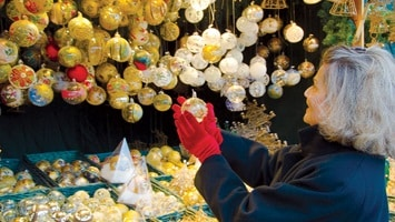 Lady in red gloves having a close look at a glass bauble at a Christmas stand