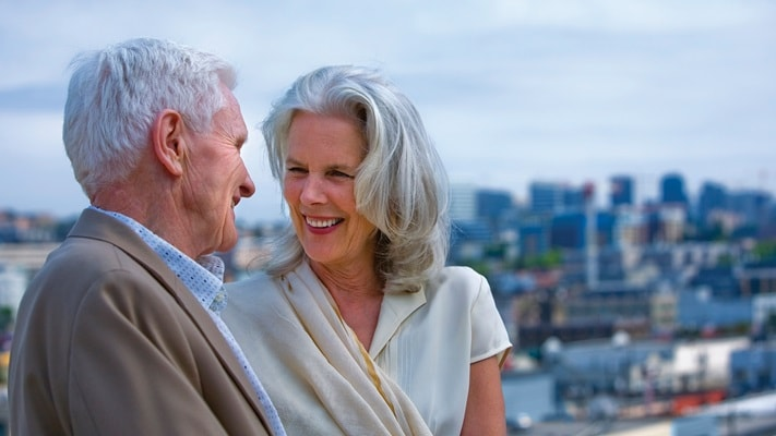 Couple standing together smiling with cityscape in the background