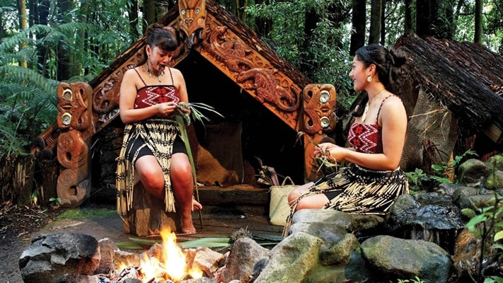 Two maori ladies weaving in a village, New Zealand