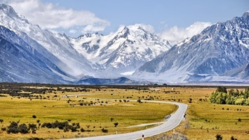 Snow capped mountains with winding road in foreground, Mount Cook National, New Zealand