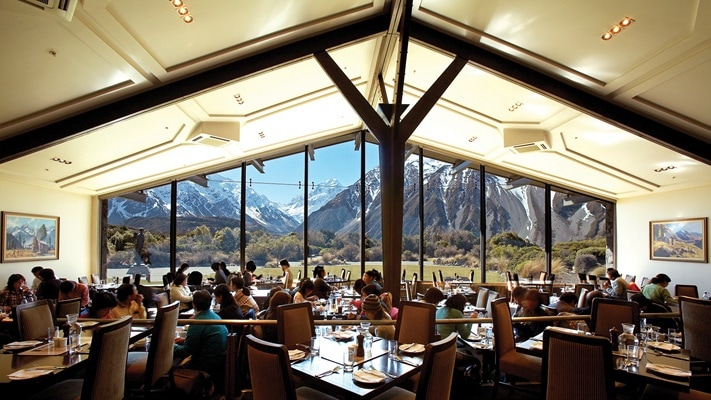 Patrons dining in hotel restaurant with cathedral ceiling and large panoramic windows all looking out over valley to mountains