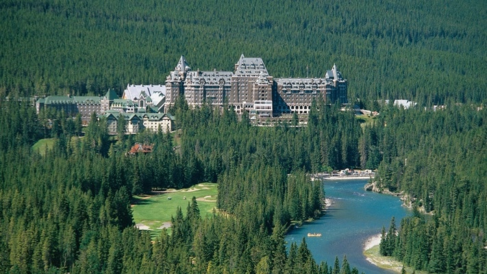 View of large hotel amongst pine forest from a distance, Canada