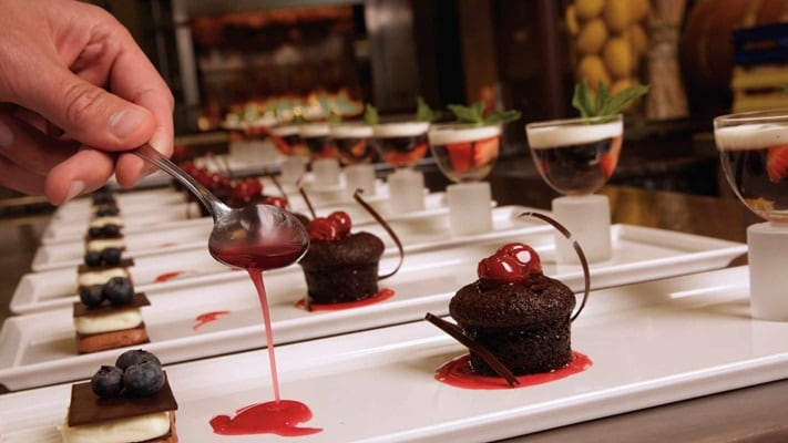 Row of rectangular plates with desserts being dressed by the chef, Canada