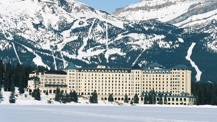 Frozen lake and hotel facade against the snowy mountain backdrop in Lake Louise, Canada