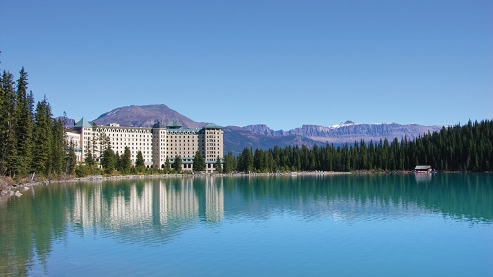 Hotel set on large lake with mountains in background, Canada