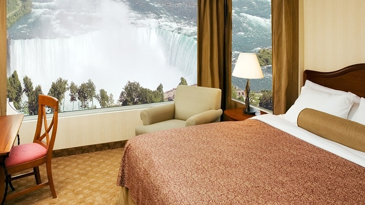 Bed near large panoramic window overlooking Niagara Falls, Canada