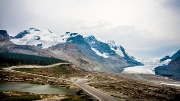 Road winding through the valley to the snow capped mountain ranges and glacier