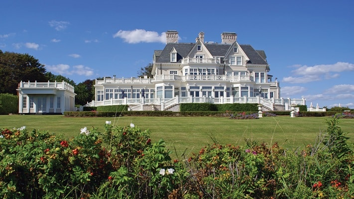 Shrubs and manicured lawns leading to the decorative, ornate white timber summer cottage in Newport, Rhode Island