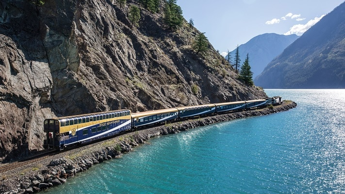 Train travelling beside torquise lake between mountain range, Canada