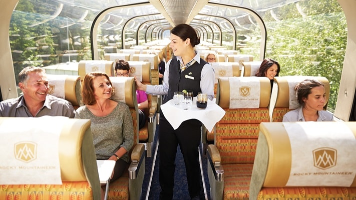 Passengers sitting in the glass domed rail carriage being served