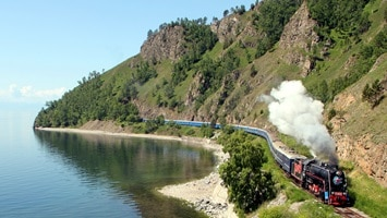 Train travelling along the coast alongside a lake, Russia