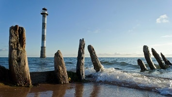 Remains of a jetty along the coastline as waves lap at the shoreline and a lighthouse in the background