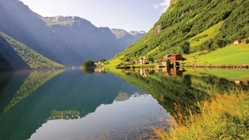 Small huts situated on the banks of the fjord on a clear bright sunny day.