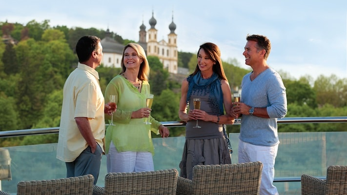 Two couples standing sharing a drink top deck of river ship with Abbey in the background