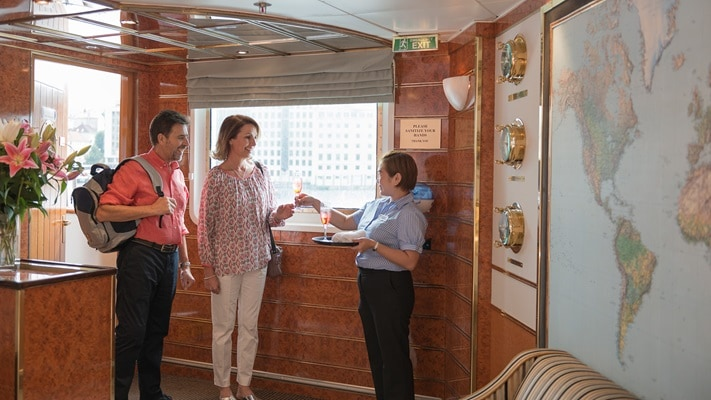 Couple receiving a welcome back on board drink from cruise staff