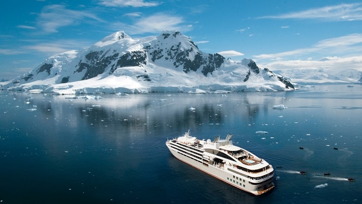 Luxury small ship cruising off the coast of Antarctica