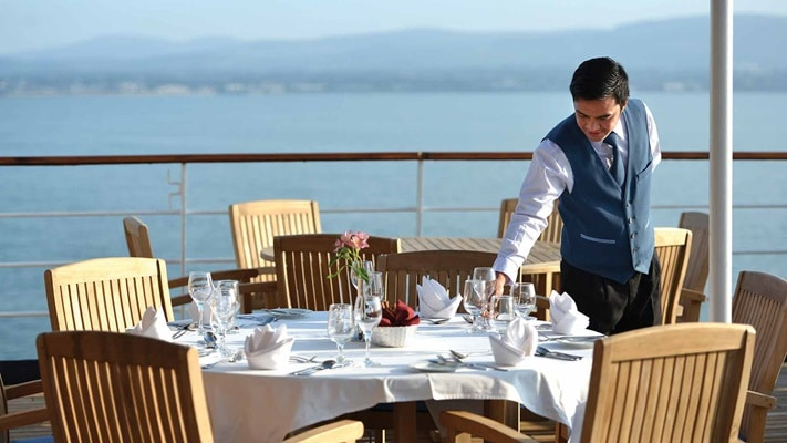 Waiter setting table on outdoor deck of ship