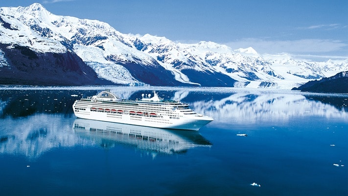 Large ocean liner in the middle of bay surrounded by high snow covered mountains