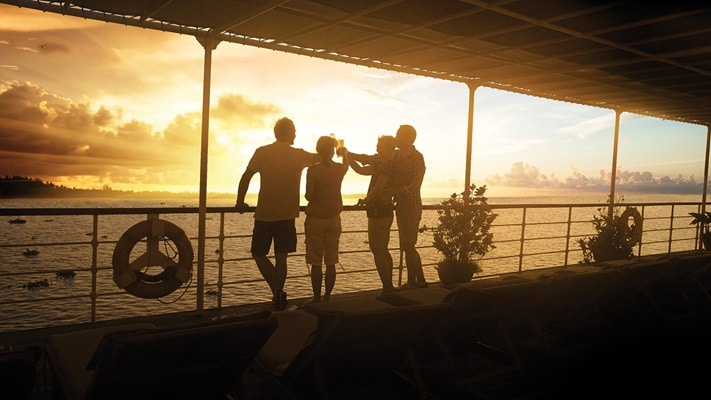 Silhouettes of couples standing on ship deck as the sun sets