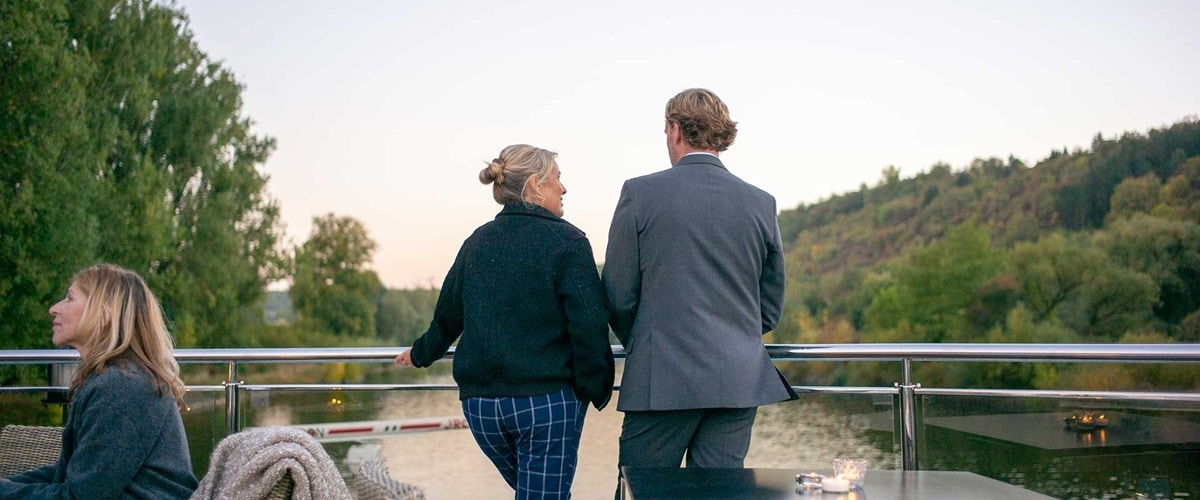 Couple standing on back deck overlooking river